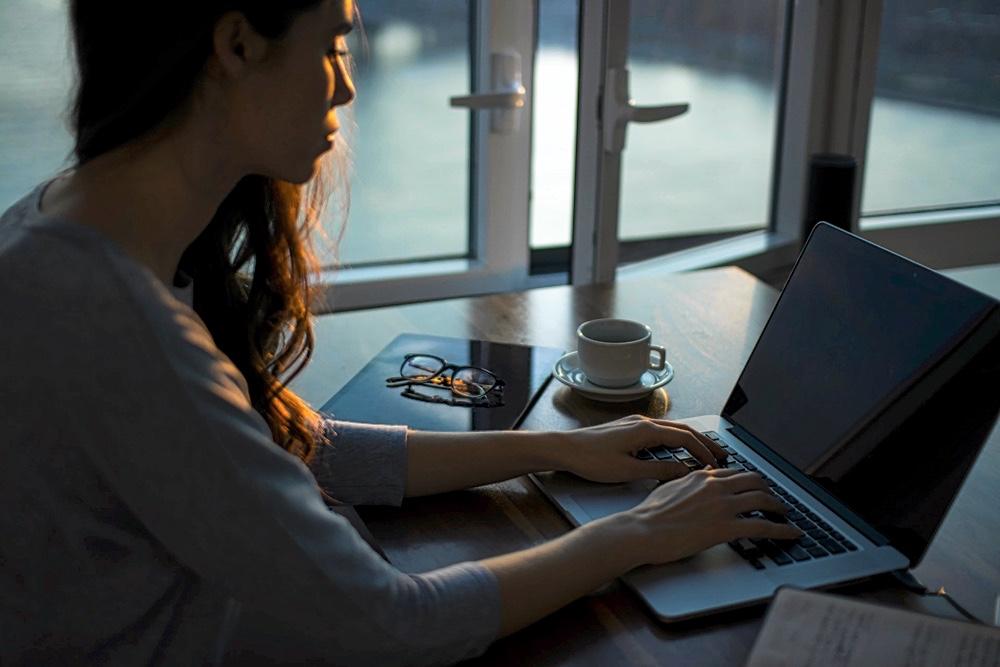 Rilettura e annotazione di un testo durante la revisione - Ragazza scrivendo al computer al tramonto