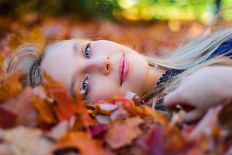 Puoi cambiare il futuro - Ragazza bionda in primo piano distesa tra le foglie autunnali